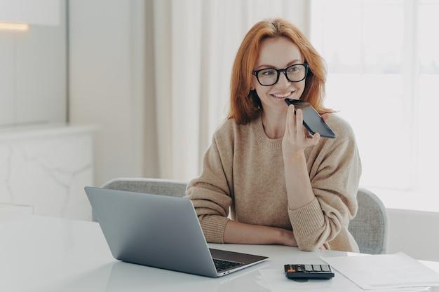 Uśmiechnięta kobieta księgowa finansista używa systemu rozpoznawania głosu na smartfonie nagrywa wiadomość dźwiękową
