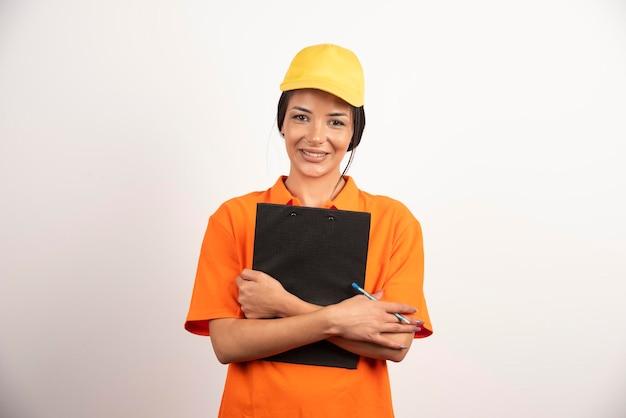 Uśmiechnięta kobieta kurier trzymając schowek na białej ścianie.