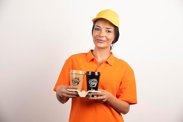 Uśmiechnięta kobieta kurier trzymająca dwie filiżanki kawy