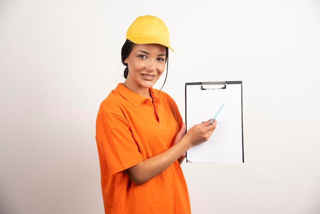 Uśmiechnięta kobieta kurier wyświetlono schowka na białej ścianie.