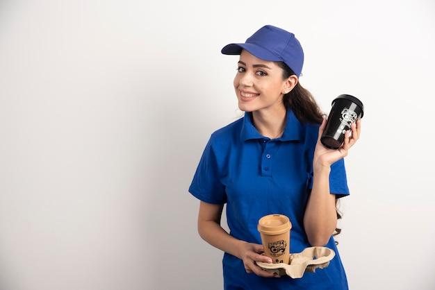 Uśmiechnięta kobieta kurier z dwiema filiżankami kawy. zdjęcie wysokiej jakości