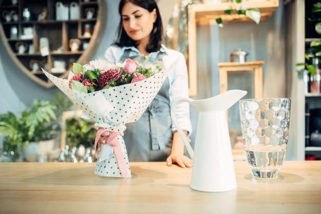 Uśmiechnięta kobieta kwiaciarni patrzy na bukiet kwiatów w sklepie kwiatowy. usługi florystyczne, działalność florystyczna