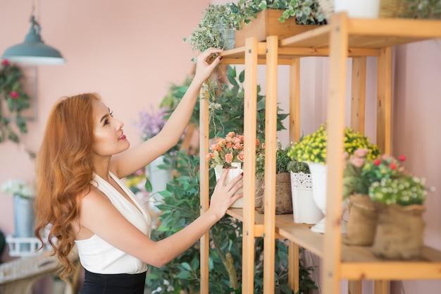 Uśmiechnięta kobieta kwiaciarnia układa piękne kwiaty w kwiaciarni