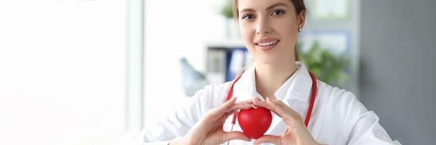 Uśmiechnięta kobieta lekarz trzymająca czerwone serce zabawki w dłoniach w klinice
