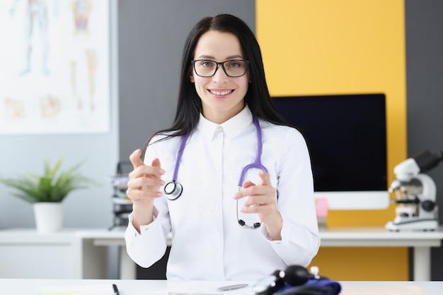 Uśmiechnięta kobieta lekarz w białym fartuchu i stetoskop w gabinecie lekarskim