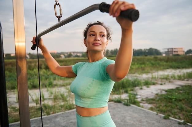 Uśmiechnięta kobieta lekkoatletka smukły african american wyginanie mięśni na maszynie siłowni. sportowa kobieta wykonywania ćwiczeń z crossover maszyna do ćwiczeń w odkrytym boisku. fitness, koncepcja kulturystyki