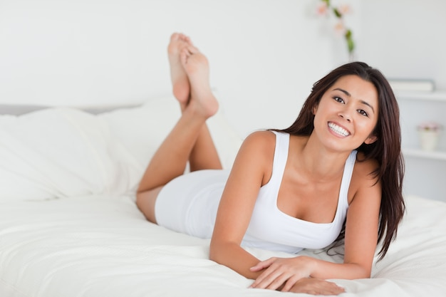 Uśmiechnięta kobieta leżąc na łóżku ze skrzyżowanymi nogami