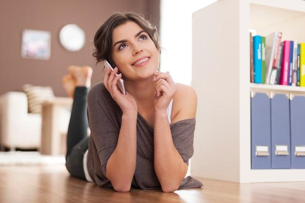 Uśmiechnięta kobieta, leżąc na podłodze i rozmawiając przez telefon komórkowy