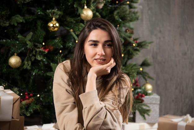 Uśmiechnięta Kobieta Leżąc Na Puszystym Dywanie Z Prezentami świątecznymi. Darmowe Zdjęcia