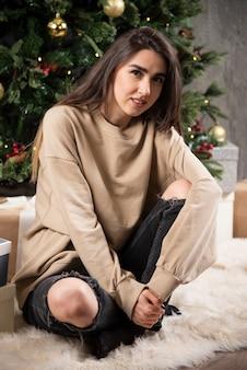 Uśmiechnięta kobieta leżąc na puszystym dywanie z prezentami świątecznymi.