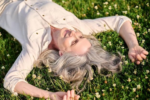 Uśmiechnięta kobieta leżąca na kwitnącej trawie