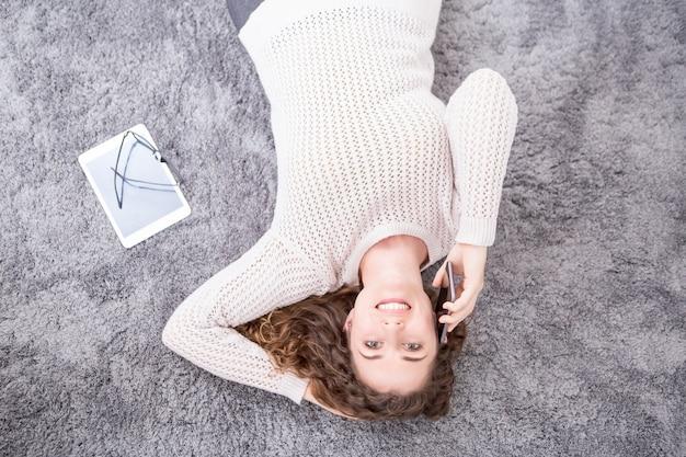 Uśmiechnięta kobieta leżącego na podłodze i wywołanie na telefon