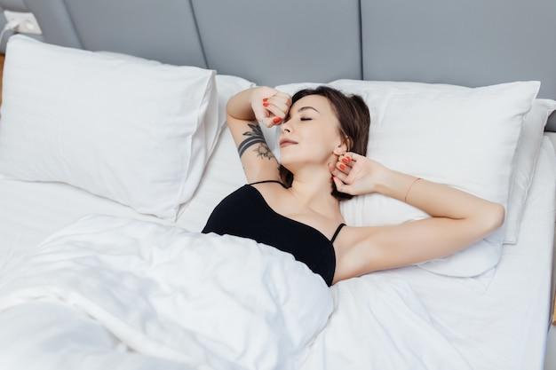 Uśmiechnięta kobieta leży na łóżku rano obudzić, rozciągając ręce i ciało