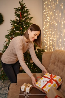Uśmiechnięta kobieta licząc prezent na boże narodzenie na kanapie w salonie w pobliżu choinki