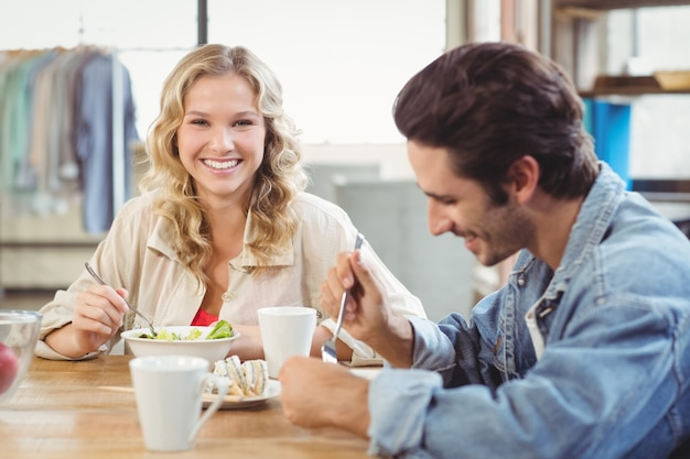 Uśmiechnięta kobieta ma śniadanie z kolegą w biurze