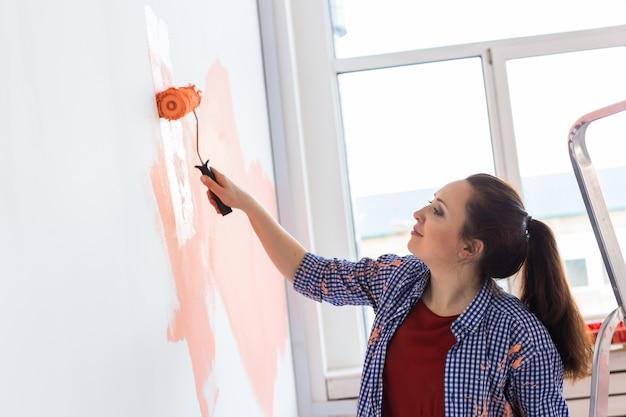 Uśmiechnięta kobieta malarstwo wewnętrzne ściany domu. koncepcja renowacji, naprawy i remontu.