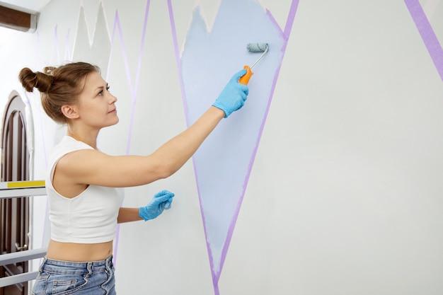 Uśmiechnięta kobieta malująca ścianę wałkiem do malowania i używająca taśmy maskującej stojąc na drabinie