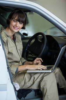 Uśmiechnięta kobieta mechanik za pomocą laptopa w garażu naprawy