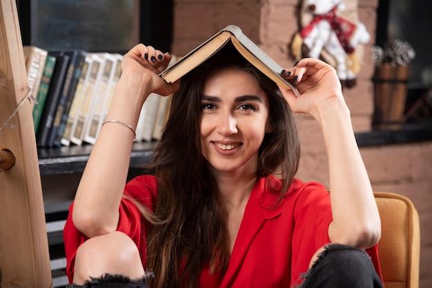 Uśmiechnięta kobieta model siedzi i trzyma książkę nad głową.