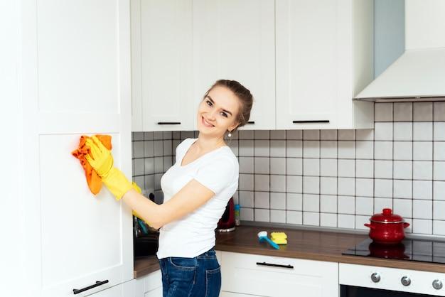 Uśmiechnięta kobieta myje szafkę lub białą lodówkę w kuchni. koncepcja czyszczenia wiosennego, firma sprzątająca