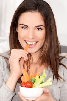 Uśmiechnięta kobieta na kanapie jedzenie sałatki jarzynowej