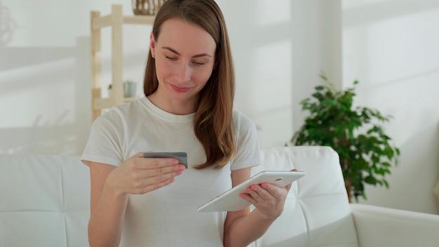 Uśmiechnięta kobieta na kanapie za pomocą tabletu i karty bankowej robi zakupy online w domu w salonie