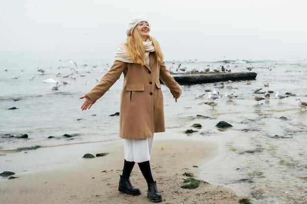 Uśmiechnięta kobieta na plaży zimą