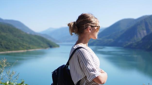 Uśmiechnięta kobieta na tle górskiego krajobrazu i jeziora. zhinvali zbiornik jezioro krajobraz z górami. główny grzbiet kaukazu.