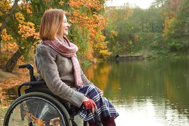 Uśmiechnięta kobieta na wózku inwalidzkim, ciesząc się pięknym widokiem na jezioro w parku w jesienny dzień