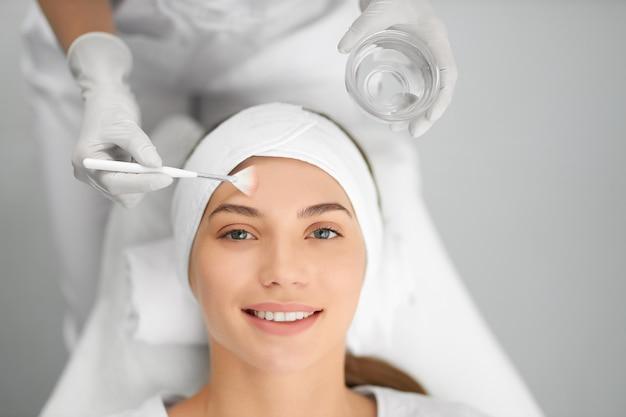 Uśmiechnięta kobieta na zabieg kosmetyczny w kosmetyczce