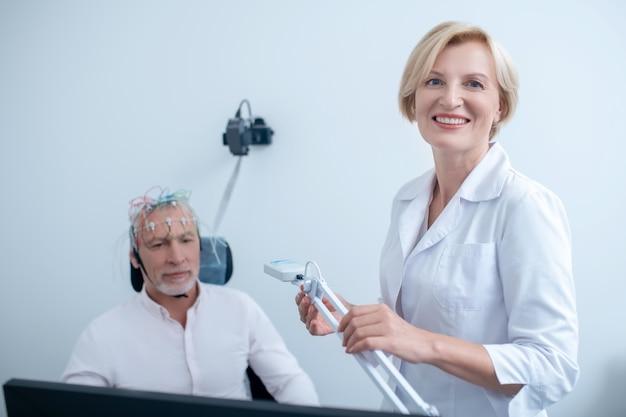 Uśmiechnięta kobieta neurolog trzymając lampę, siwowłosy pacjent przechodzi elektroencefalogram