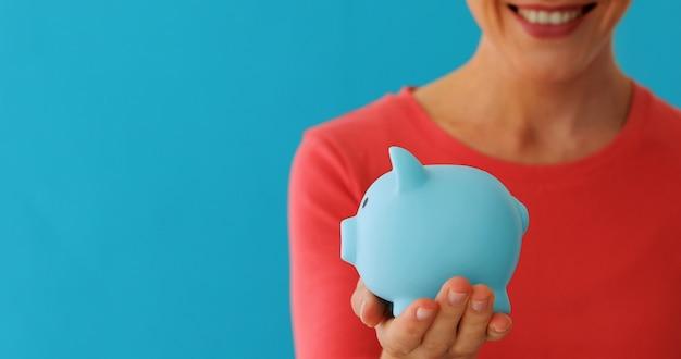 Uśmiechnięta kobieta niesie prosiątko banka