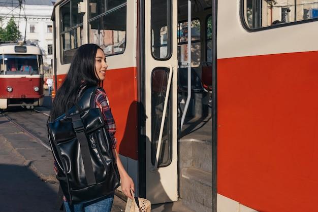 Uśmiechnięta kobieta niosąca plecak i trzymając kapelusz stoi przed drzwi włóczęgi