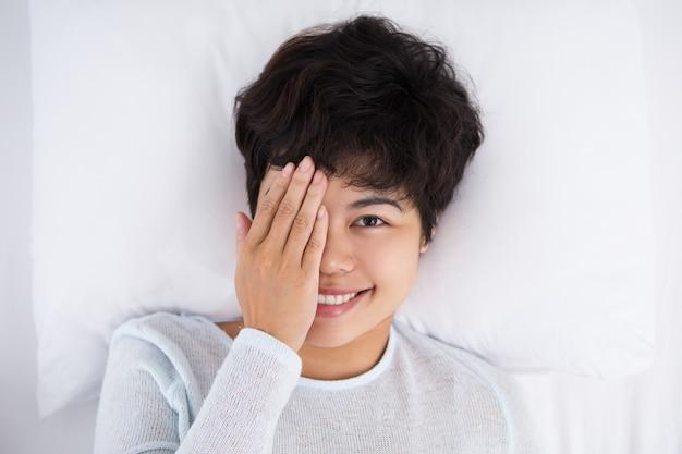 Uśmiechnięta kobieta obejmujące jedno oko i leżącego w łóżku