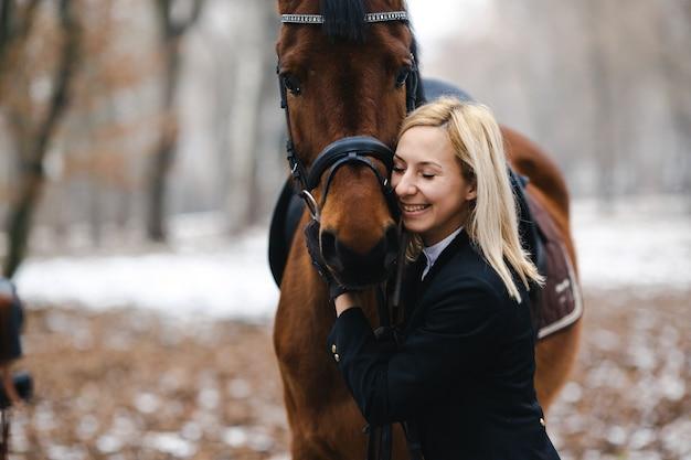 Uśmiechnięta kobieta obejmującego konia