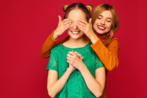 Uśmiechnięta kobieta obejmujących oczy rękami do swojego przyjaciela
