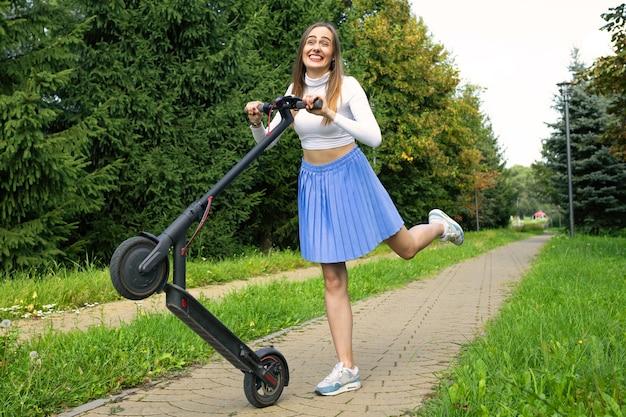 Uśmiechnięta kobieta oddaje się hulajnodze elektrycznej w parku