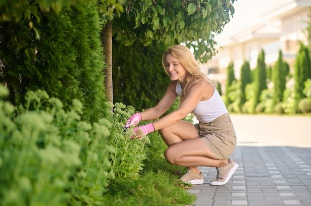 Uśmiechnięta kobieta ogrodnicza przyczajona w pobliżu kwiatów