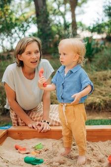 Uśmiechnięta kobieta opiekująca się dzieckiem w piaskownicy