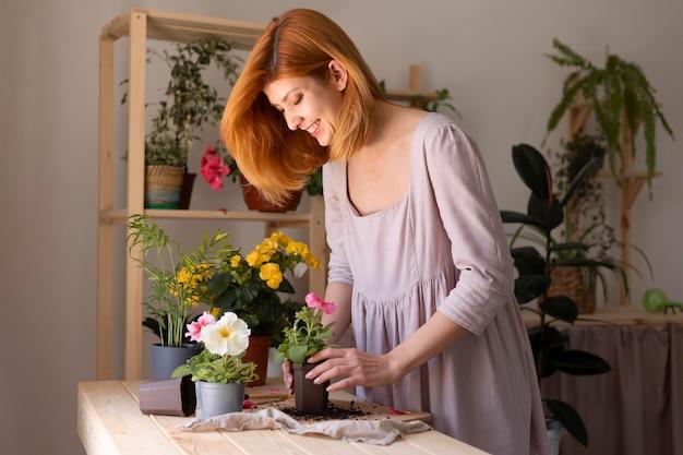 Uśmiechnięta kobieta opiekująca się kwiatem średnim strzałem
