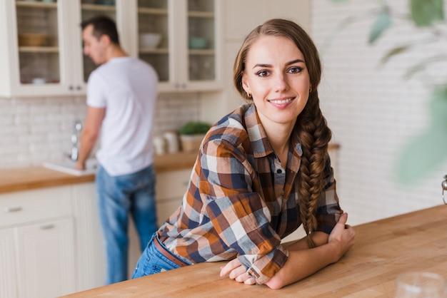 Uśmiechnięta kobieta opierając się na stole, podczas gdy człowiek mycia naczyń