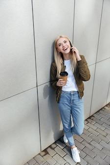 Uśmiechnięta kobieta opowiada na smartphone z kawą