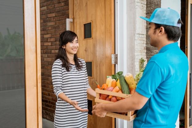 Uśmiechnięta Kobieta Otrzymywa Sklep Spożywczy Dostawę W Domu Premium Zdjęcia