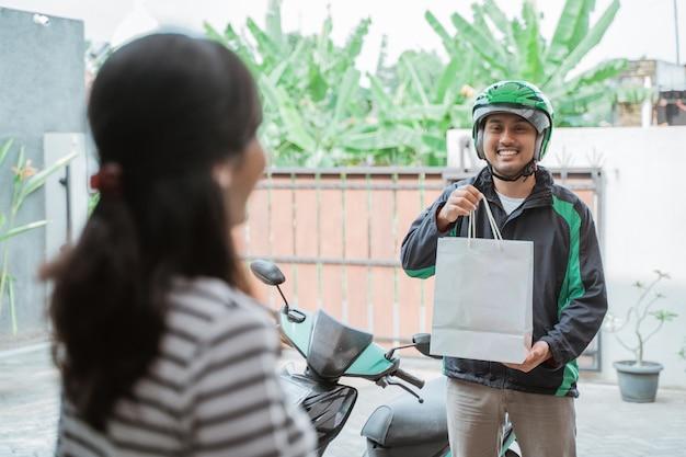 Uśmiechnięta kobieta otrzymywa sklep spożywczy dostawę w domu