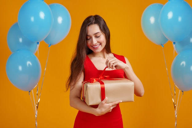 Uśmiechnięta kobieta otwiera pudełko z czerwonymi wstążkami. ładna osoba płci żeńskiej dostała niespodziankę, imprezę lub uroczystość urodzinową, dekorację balonów