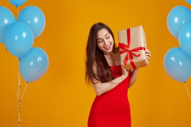 Uśmiechnięta kobieta otwiera pudełko z czerwonymi wstążkami, żółte tło. ładna osoba płci żeńskiej dostała niespodziankę, imprezę lub uroczystość urodzinową, dekorację balonów