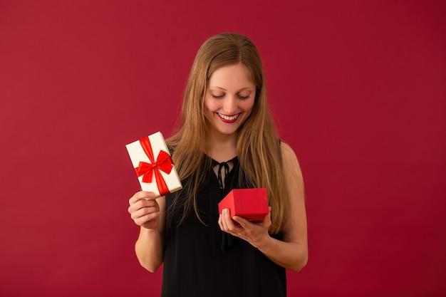 Uśmiechnięta kobieta, otwierając pudełko ze wstążką na czerwonym tle.