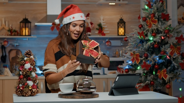 Uśmiechnięta kobieta otwierająca prezent od przyjaciół podczas rozmowy wideo