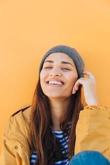 Uśmiechnięta kobieta patrząc na kamery siedzi przed żółtej powierzchni