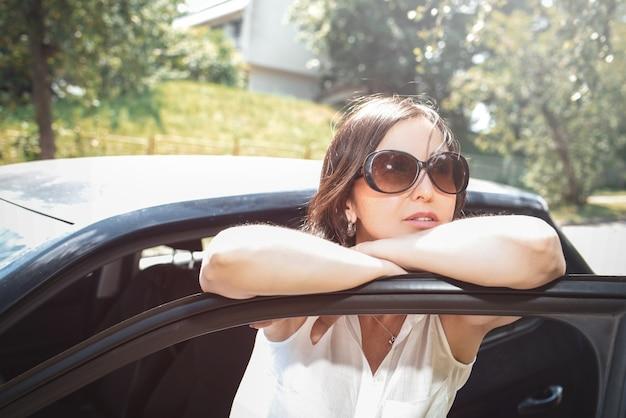 Uśmiechnięta kobieta patrząc na samochód w okularach przeciwsłonecznych